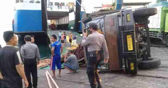Keluar dari Kapal, Truk Pengangkut Kayu Terguling