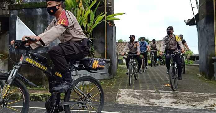 Masuk Zona Merah, Polisi Gianyar Sosialisasi Prokes Sambil Bersepeda
